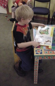 Jayden reads in the kids room.